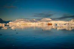 Een boot die onder de reusachtige ijsbergen, Ilulissat Icefjord, Groenland varen royalty-vrije stock fotografie