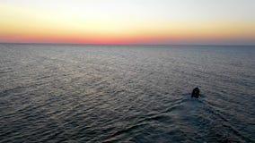 Een boot die op het overzees, vroeg in de ochtend, mooie zonsopgang als achtergrond varen Luchtmeningszeegezicht Plaatselijke bev stock video