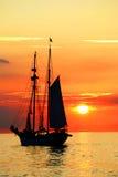 Een boot die tegen zonsondergang varen Stock Afbeelding