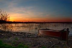 Een boot door het meer bij zonsondergang royalty-vrije stock afbeelding