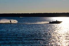 Een boot en waterskiër tegen een blauw meer wordt gesilhouetteerd dat stock fotografie