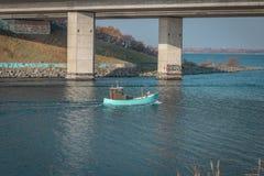 Een boot gaat onder een brug over in Svenskeholm stock afbeelding