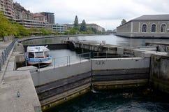 Een boot gaat een slot op de rivier van de Rhône in Genève over stock fotografie