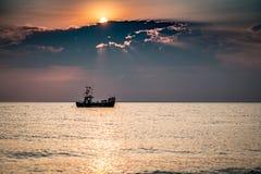 Een boot op het overzees bij zonsopgang royalty-vrije stock afbeelding