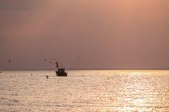 Een boot op het overzees bij zonsopgang royalty-vrije stock afbeeldingen