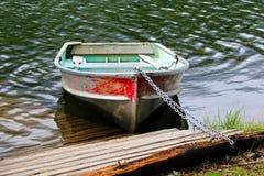 Een boot van de aluminiumrij aan de kust door een dok wordt geketend dat royalty-vrije stock fotografie