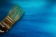 Een borstel op een blauwe nacreous kleur schilderde achtergrond royalty-vrije stock afbeelding