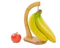 Een bos van bananen en een appel die op wit wordt geïsoleerdd Stock Fotografie