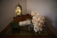 Een bos van elegante rozen zit op een lijst met een antieke gouden klok royalty-vrije stock fotografie