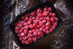 Een bos van frambozen in de zwarte schotel op de lijst Royalty-vrije Stock Foto