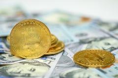 Een bos van gouden bitcoinmuntstukken die de achtergrond van meer dan honderd dollarsrekeningen leggen royalty-vrije stock fotografie