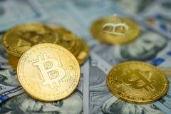 Een bos van gouden bitcoinmuntstukken die de achtergrond van meer dan honderd dollarsrekeningen leggen stock foto