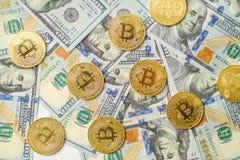 Een bos van gouden bitcoinmuntstukken die de achtergrond van meer dan honderd dollarsrekeningen leggen royalty-vrije stock foto's