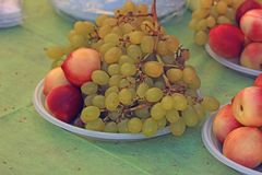 Een bos van groene druiven en perziken op een plaat Royalty-vrije Stock Afbeeldingen