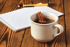 Een bos van kaneel breide met een kabel, een kop van koffie en een notitieboekje voor het schrijven op een houten close-up als ac royalty-vrije stock foto's
