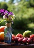 Een bos van purpere bloemen op een lijst in de tuin op een zonnige de zomerdag, dichtbijgelegen vruchten en bessen royalty-vrije stock afbeelding