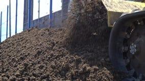 Een bouwbulldozer op rupsbanden maakt weg de grond en de aandrijving los stock video