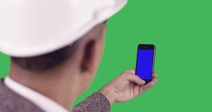 Een bouwer houdt een mobiele telefoon met het blauw scherm stock footage
