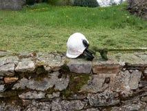 Een bouwvakker, beschermende brillen en een grasmaaier op een vers gesneden open plek stock afbeelding