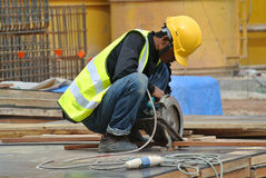 Een bouwvakker die de draagbare machine voor alle doeleinden van de pijpsnijder met behulp van Royalty-vrije Stock Afbeelding