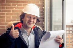 Een bouwvakker die zijn duim-omhooggaand voor een onlangs geconstrueerde woningbouw geven Zachte gestemde nadruk, stock foto
