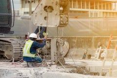 Een bouwvakker in het groene vest en de witte helm werkt met de machine in het bouwgebied royalty-vrije stock foto's