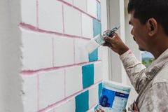 Een Bouwvakker Painting een Huis stock fotografie