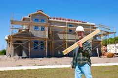 De bouw van het huis met een contractant op het werk Stock Foto