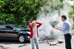 Een boze rijpe man en een jonge vrouw die na een auto debatteren verpletteren stock foto