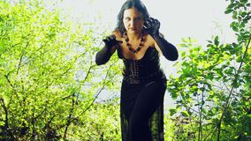 Een boze vrouwenheks in zwarte kleren op de kust van het meer Halloween Gothickstijl stock video