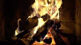 Een brand brandt in een baksteenopen haard, houdt warm stock videobeelden