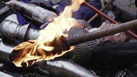 Een brandende toorts met kreupelbosjes van middeleeuwse militairen op de achtergrond stock video