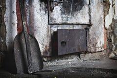 Een brandijzer en een kleine schop zijn dichtbij de oven Royalty-vrije Stock Fotografie