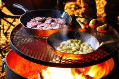 Een branding en grasmaaltijd die op een kampvuur worden gekookt stock afbeelding
