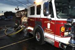 Een brandvrachtwagen heeft slangen in bijlage bij een de bouwbrand royalty-vrije stock afbeelding