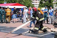 Een brandweerman in een vuurvast kostuum en een helm die een brandslang houden bij de concurrentie van de brandsport Minsk, Wit-R stock foto