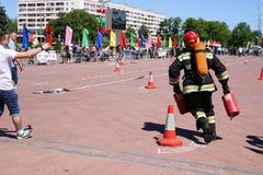 Een brandweerman in een vuurvast kostuum en een helm die met rode brandblusapparaten aan Wit-Rusland, Minsk, 08 lopen 08 2018 stock afbeelding