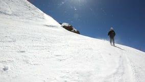 Een brede hoek mannelijke skiër verouderde in zwart materiaal en witte helm met skistokkenritten op een sneeuwhelling op een zonn stock video