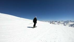 Een brede hoek mannelijke skiër verouderde in zwart materiaal en witte helm met skistokkenritten op een sneeuwhelling op een zonn stock videobeelden
