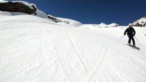 Een brede hoek mannelijke skiër verouderde in zwart materiaal en witte helm met skistokkenritten op een sneeuwhelling op een zonn stock footage