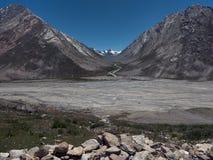 Een brede morenevallei in Zanskar: een grote die stroomstromen langs het rivierbed, in de achtergrondgletsjerpieken wordt ineenge Stock Fotografie