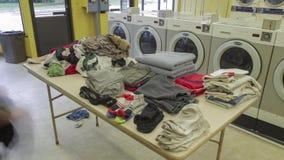 Een Breed Hoekschot van een Persoon die en vers Schoongemaakte Wasserij vouwen sorteren bij Laundromat 4K UHD Timelapse stock video
