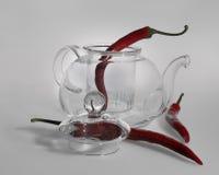 Een breekbare transparante glastheepot, een deksel van een ketel met een grote kom die zij aan zij en drie roodgloeiende peper li Royalty-vrije Stock Foto's