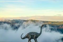 Een brontosaurus of donderhagedisdinosaurus die tegen een vage nevelige die bergachtergrond brullen - met een model tegen natur w stock foto's