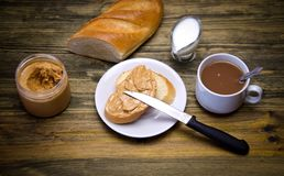 Een brood van brood en een sandwichstuk van brood met pindakaas en mes, Kop en melkkruik  royalty-vrije stock afbeelding