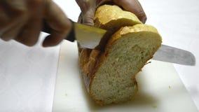 Een brood van brood met een mes wordt gesneden dat stock footage