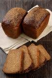 Een brood van roggebrood met plakken Stock Afbeelding