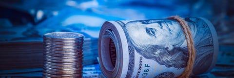 Een broodje van dollars met muntstukken op de achtergrond van verspreide honderd dollarsrekeningen in blauw licht stock foto's