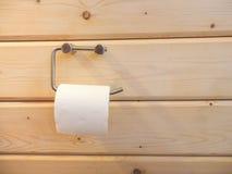 Een broodje van toiletpapier het hangen op een houder met houten muur Stock Fotografie