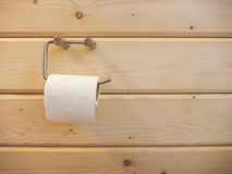 Een broodje van toiletpapier het hangen op een houder met houten muur Royalty-vrije Stock Foto's